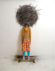 Afro Charlie. 2009 Instalación. Figura de una adolescente a tamaño real, tallada en madera policromada, patineta y dibujo al carbón sobre pared.