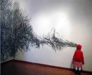 El bosque. 2004 Instalación. Figura de niña tamaño real tallada en madera, textil, grafito. Medidas variables. Colección Cisneros