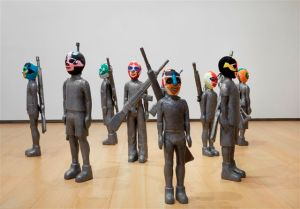 Mambrú. 2005 Instalación.  Talla en madera de cedro de la figura de niños de 8 a 12 años al tamaño real. Recubierto de laminas de plomo. Máscaras de