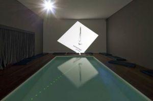 """4. cosmococa CC4, Nocagions, rend hommage à John Cage e au """"blanc sur blanc » suprématiste de de Malevitch. L'œuvre permet une expérience plus radicale avec l'immersion dans la piscine à l'intérieur de laquelle seulement on perçoit les lumières vertes et bleues qui l'entourent."""