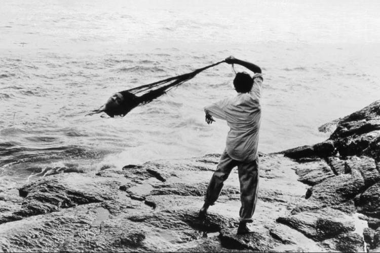 Semant des sirènes, 1987, photo de performance, où Tunga jetait à la mer un moulage de sa tête , partie d'une installation Arpoador, Rio de Janeiro